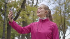 Portrait of smiling Caucasian sportswoman in pink sportswear talking through videochat and showing thumb up. Cheerful. Girl training in the morning outdoors stock video footage