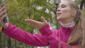 Portrait of smiling Caucasian woman in pink sportswear sending air kisses via smart phone and starting running. Female. Runner training in the morning outdoors stock video
