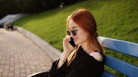 Portrait of smiling caucasian woman with red hair talking on cellphone while resting on the bench in summer park. Cheerful beautiful female calling on mobile stock video footage