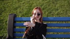 Portrait of smiling caucasian woman with red hair talking on cellphone while resting on the bench in summer park. Cheerful beautiful female calling on mobile stock video