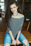 Caucasian young beautiful woman model with messy long hair in ripped blue jeans and striped t-shirt sitting on table Stock Images
