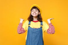 Portrait of smiling charming girl teenager in french beret, denim sundress spreading hands isolated on yellow wall royalty free stock photography