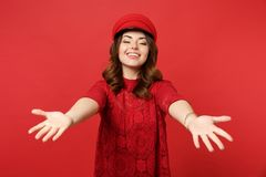 Portrait of smiling charming young woman in lace dress cap standing with outstretched hands isolated on bright red stock photography