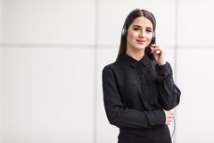 Portrait of smiling cheerful customer support phone operator in headset. Against office background Stock Photos