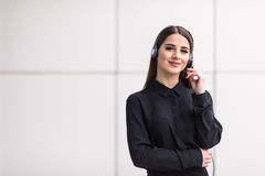 Portrait of smiling cheerful customer support phone operator in headset. Against office background Royalty Free Stock Photos