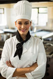 Portrait of smiling chef head standing with arms crossed. Portrait of chef head standing with arms crossed in commercial kitchen royalty free stock photo