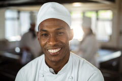Portrait of smiling chef. Portrait of smiling head chef standing in commercial kitchen stock photo