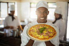 Portrait of smiling chef showing pizza Royalty Free Stock Image