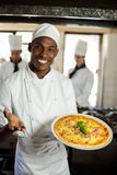 Portrait of smiling chef showing pizza Stock Photography