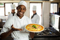 Portrait of smiling chef showing pizza Royalty Free Stock Photos