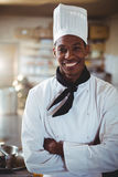 Portrait of smiling chef standing with arms crossed. In commercial kitchen royalty free stock photos