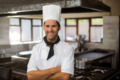 Portrait of smiling chef standing with arms crossed. In commercial kitchen royalty free stock photography