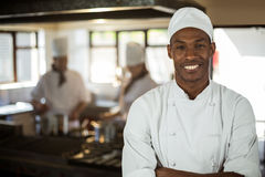 Portrait of smiling chef standing with arms crossed. In commercial kitchen royalty free stock photo