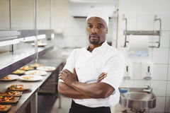 Portrait of smiling chef standing with arms crossed in commercial kitchen. At restaurant stock images