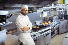 Portrait of smiling chef standing with arms crossed in commercial kitchen Royalty Free Stock Photos