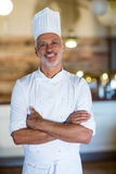 Portrait of smiling chef standing with arms crossed. In restaurant stock photo