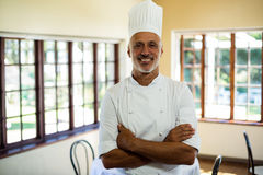 Portrait of smiling chef standing with arms crossed. In restaurant stock image
