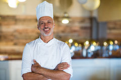 Portrait of smiling chef standing with arms crossed. In restaurant stock images