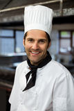 Portrait of smiling chef. Standing in commercial kitchen royalty free stock images