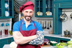 Portrait of Smiling chef with tattooed hand in apron and cap on kitchen background royalty free stock photo