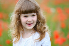 Portrait of a smiling child with blooming red flowers as backgro Stock Photo