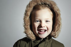 Portrait of Smiling child in fur hood and winter jacket. fashion kid.children.parka.little boy winter style Royalty Free Stock Photography