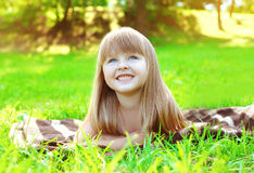 Portrait of smiling child lying resting on the grass in summer Royalty Free Stock Image