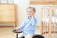 Portrait smiling  child riding toy vintage car. Funny kid playing at home. Summer vacation and travel concept. little boy driving. A car in the nursery. Toddler royalty free stock images
