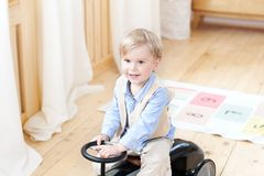 Portrait smiling  child riding toy vintage car. Funny kid playing at home. Summer vacation and travel concept. little boy driving. A car in the nursery. Toddler stock photo