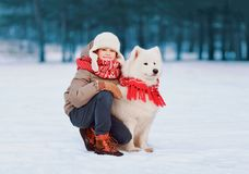 Portrait of smiling child walking with white Samoyed dog in winter stock photography