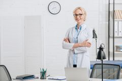 portrait of smiling chiropractor in eyeglasses and white coat standing at workplace