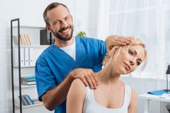 portrait of smiling chiropractor stretching neck of woman