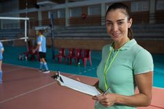 Portrait of smiling coach holding clipboard at volleyball court Stock Photos