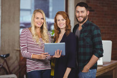 Portrait of smiling colleagues holding digital tablet Stock Photography