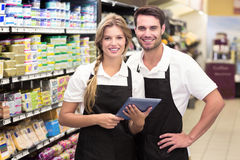 Portrait of smiling colleagues using a digital tablet. At supermarket Stock Image