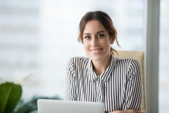Portrait of smiling confident female boss looking at camera. Portrait of smiling beautiful millennial businesswoman or CEO looking at camera, happy female boss stock photo