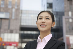 Portrait of smiling confident young businesswoman, outdoors with building exterior in background in Beijing, China Royalty Free Stock Images