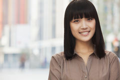 Portrait of smiling, confident, young woman with bangs and long hair, outdoors in Beijing, China. Portrait of smiling, confident, young women with bangs and long stock image