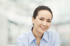 Portrait of smiling confident young woman in button down shirt, looking into camera Royalty Free Stock Images