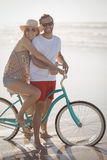 Portrait of smiling couple with bicycle on shore at beach Stock Photo