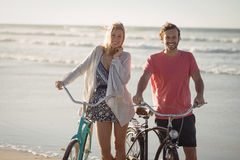 Portrait of smiling couple with bicycles standing at beach Stock Photography