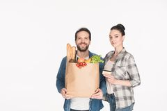 Portrait of smiling couple with credit card and paper package with grocery. On white royalty free stock photography