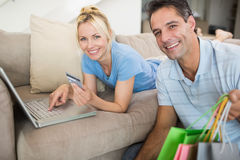 Portrait of smiling couple doing online shopping at home Stock Photography