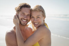 Portrait of smiling couple embracing at beach Stock Image