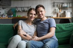 Portrait of smiling couple embracing looking at camera at home royalty free stock image