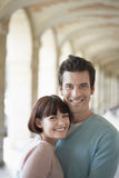Portrait Of Smiling Couple Embracing Under Archway Stock Photo