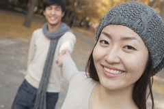 Portrait of Smiling Couple Holding Hands in Park Royalty Free Stock Photography