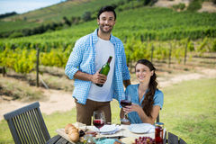Portrait of smiling couple holding red wine bottle and glass Royalty Free Stock Images