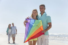 Portrait of smiling couple with kite on sunny beach royalty free stock images