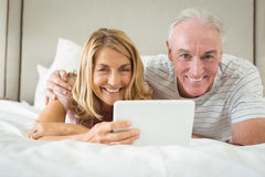 Portrait of smiling couple lying on bed and using laptop Royalty Free Stock Images